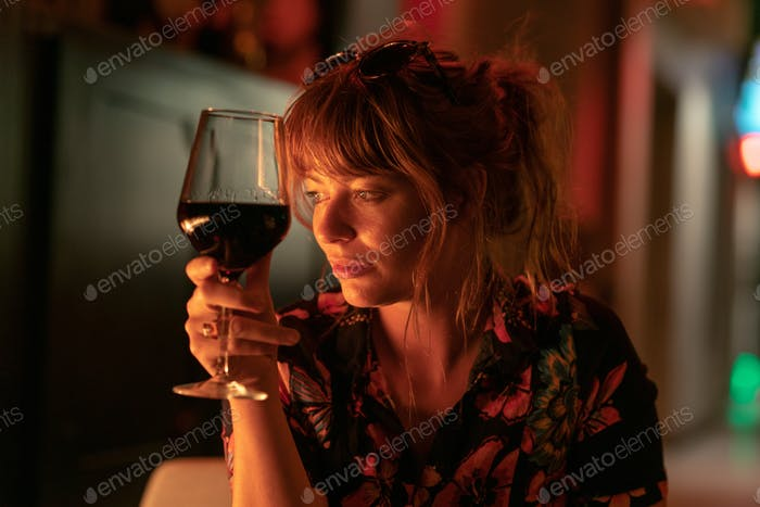Beautiful ginger girl drinking a glass of red wine near a fire pit