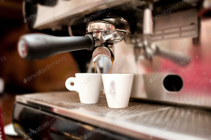espresso machine pouring coffee in cups
