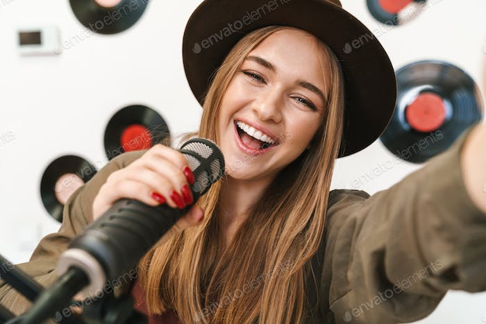 Image of young woman at radio making podcast recording for online show