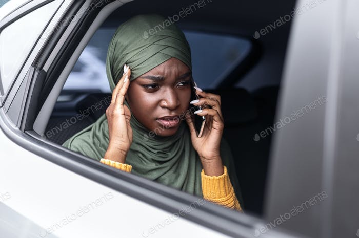 Stressed black muslim lady riding car on backseat and talking on cellphone