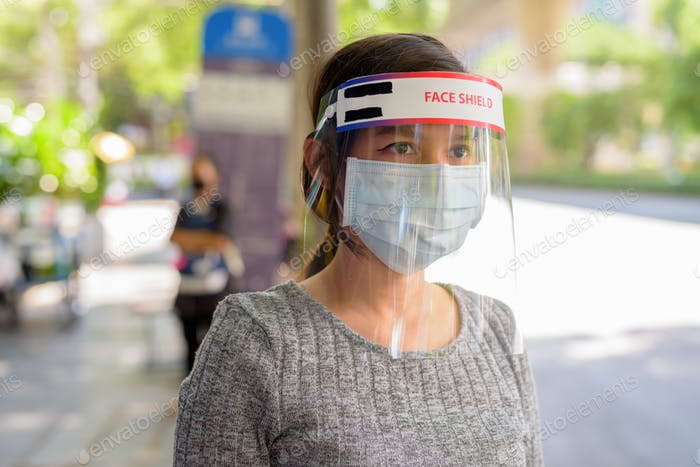 Face of young Asian woman wearing mask and face shield while waiting at the bus stop