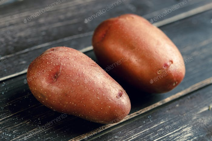 Fresh potatoes on the wood background. Close up