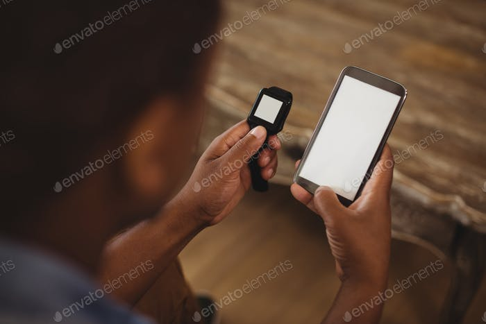 Man using smartwatch and smartphone