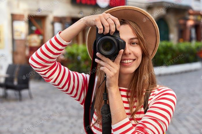 Professioneller Fotograf macht Amateurfotos während eines Ausflugs in der Stadt, lächelt Positi