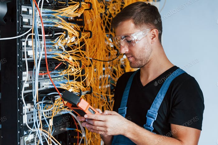 Young man in protective glasses works with internet equipment and wires in server room