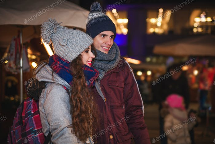 Young couple walking at evening on traditional Christmas market, fairy place