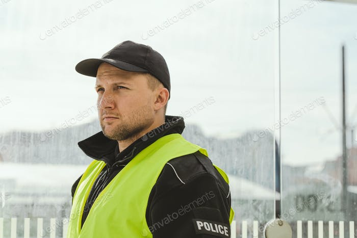 Handsome police officer wearing black uniform and reflecting vest