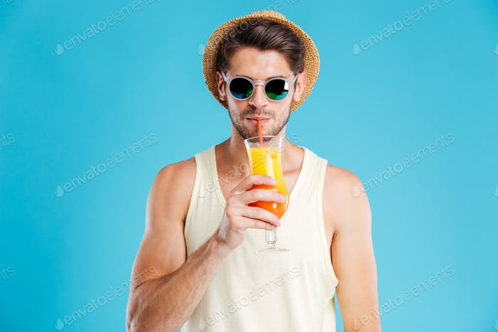 Attractive young man in hat and sunglasses drinking orange juice