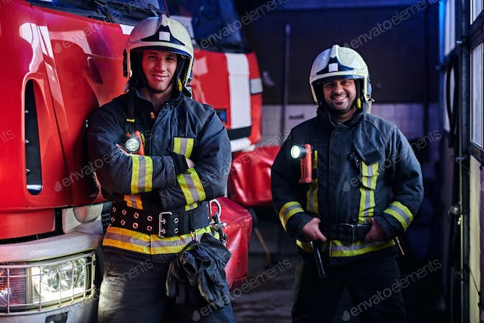 Two firemen standing near the fire truck at night in a fire depot