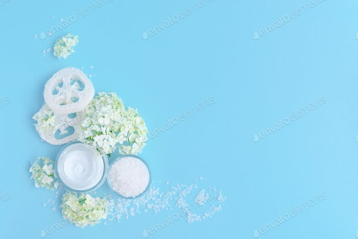 Spa composition with cream, salt, sponges and flowers on a blue