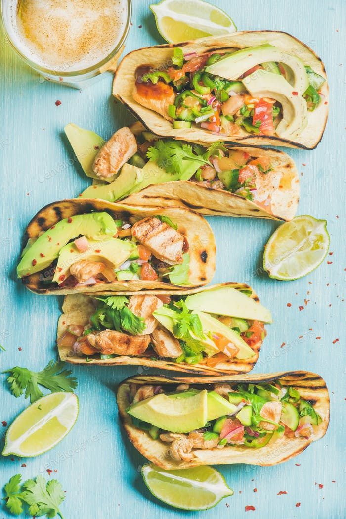 Healthy corn chicken tortillas and beer over blue wooden background