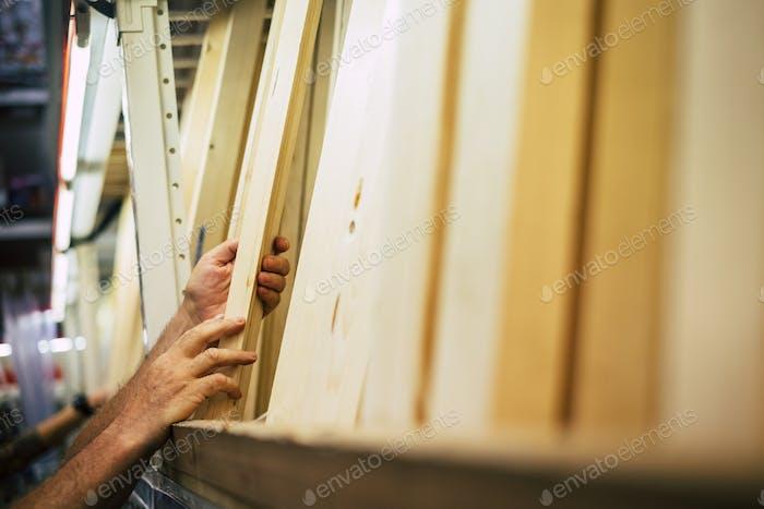 manos hombre elegir un pedazo de madera para construir o reparar las cosas en casa