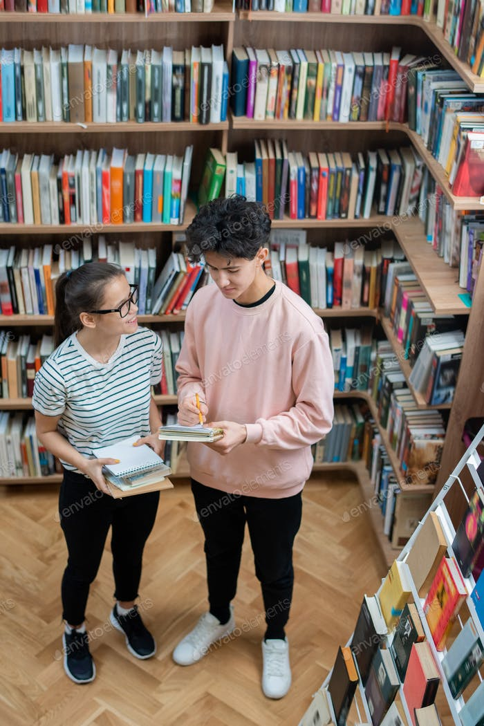 Two casual teenagers standing in college library among shelves with books