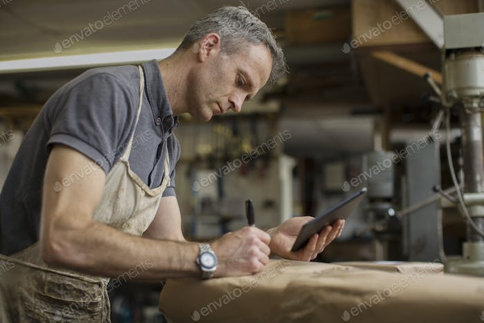 A man in a furniture restoration workshop using a digital tablet, writing on a packet wrapped in