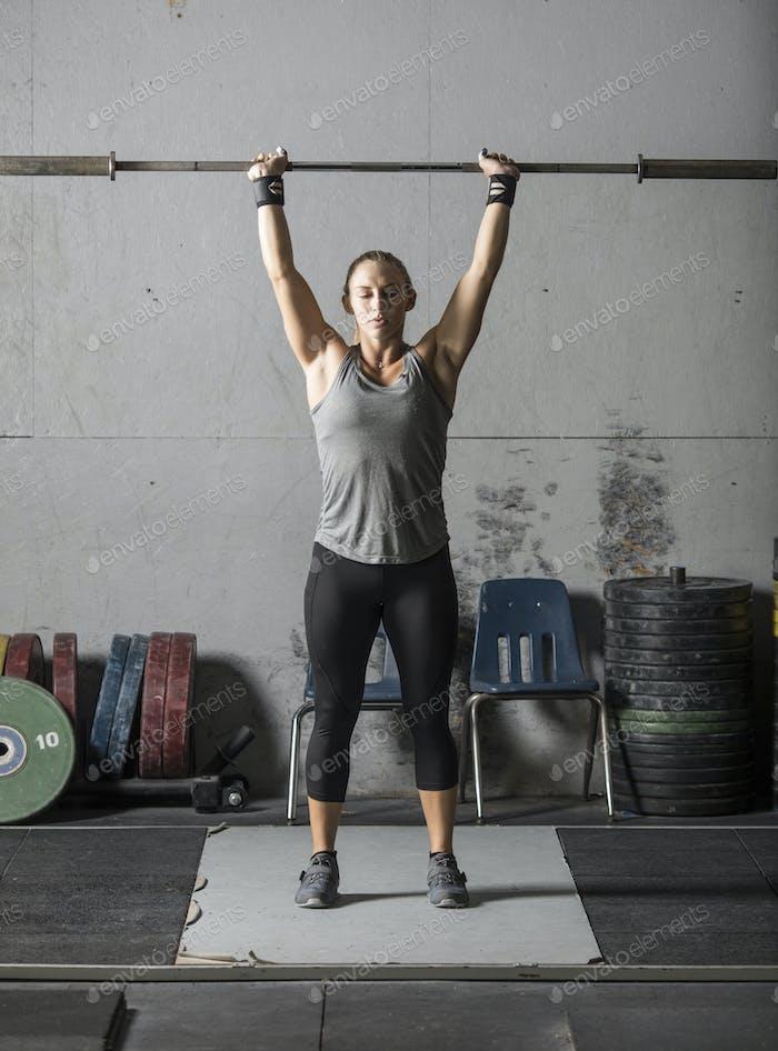 Junge Frau wärmt sich auf und macht sich bereit für schweres Heben im Fitnessstudio.