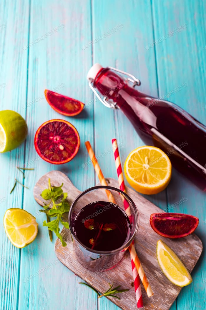 Summer berry juice in a glass bottle with citrus on blue wooden background