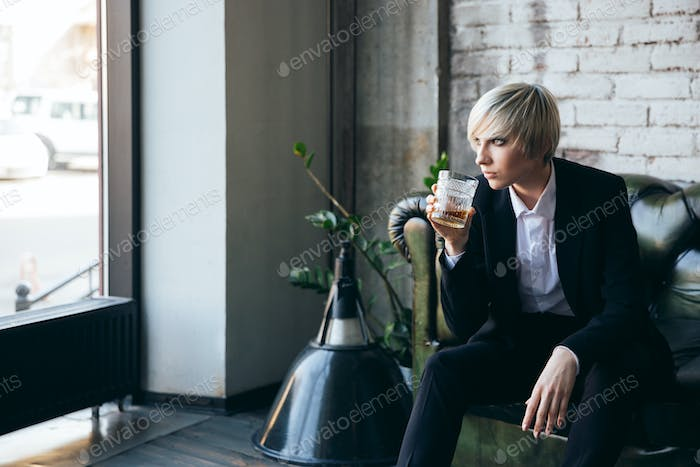 Stylish blonde girl drinking alcohol in a cafe