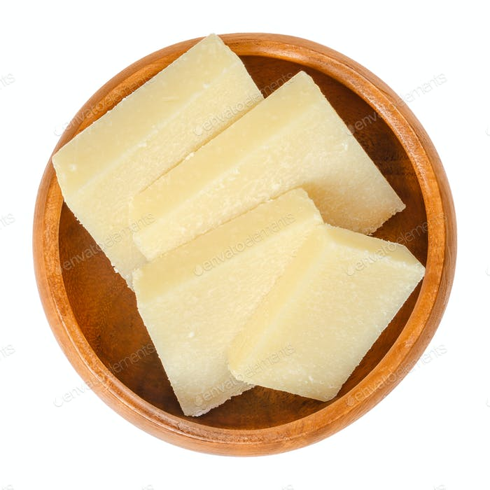 Parmesan cheese pieces in wooden bowl over white
