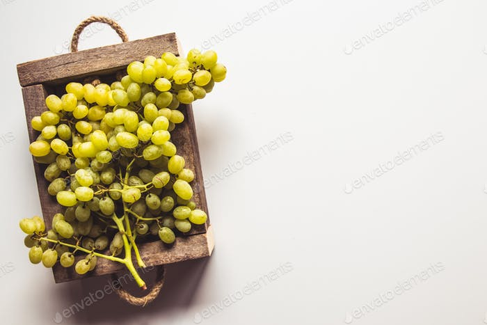 Wooden box with red grapes isolated on white background