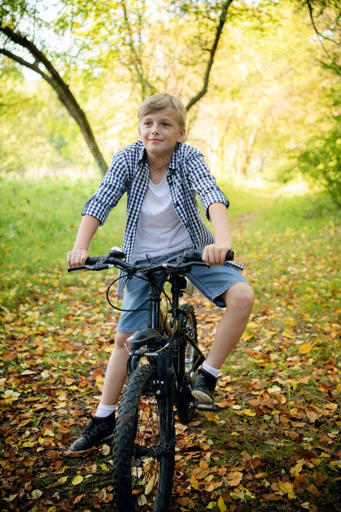 Preteen handsome boy with bicycle on the forest path