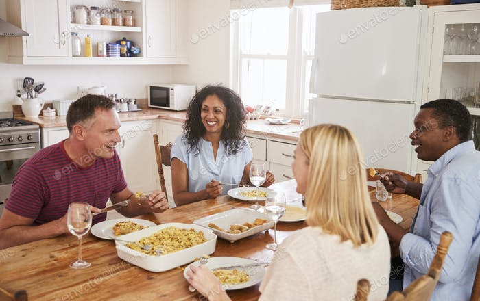 Mature Couple Entertaining Friends At Dinner Party