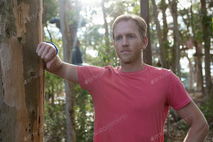 Man standing in forest taking support of tree