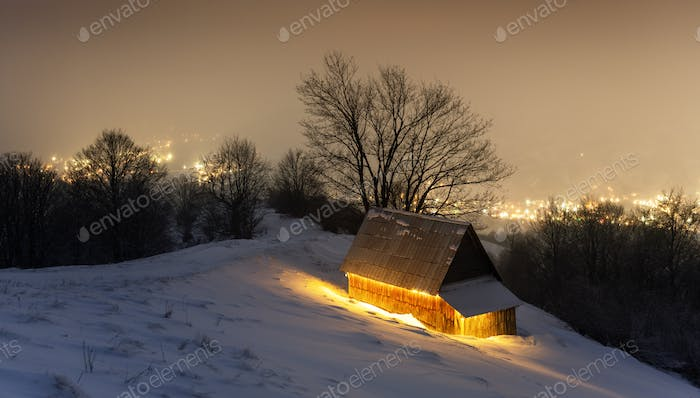 Fantastic winter landscape with glowing wooden house