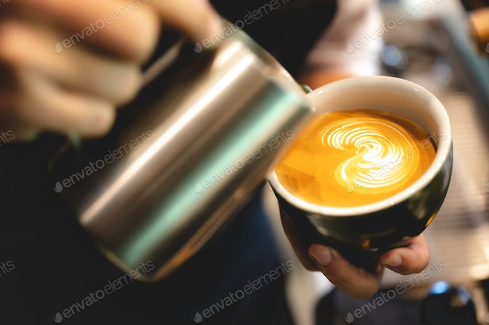 professional barista making latte art from coffee and milk, hand holding a cup of latte