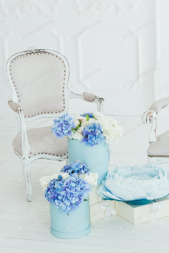 Light vintage style armchair and boxes of flowers