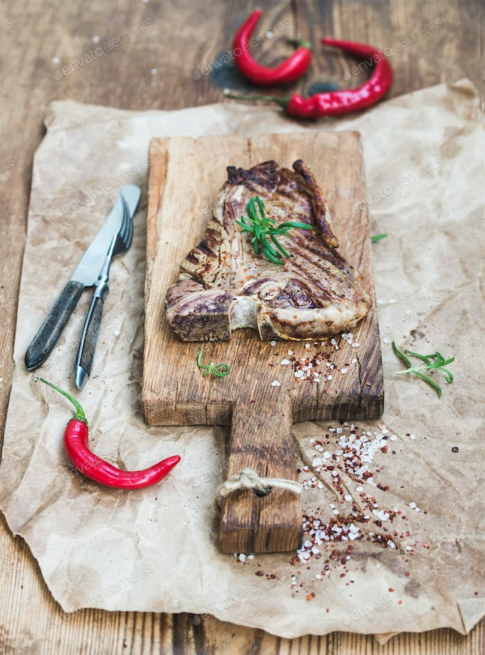 Cooked meat t-bone steak on serving board with red chili peppers, spices, fresh rosemary