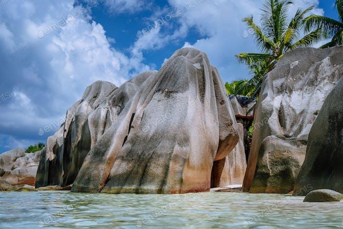 Anse Source d'Argent -Riesige Granitfelsen zwischen Palbäumen am tropischen Sandstrand gegen