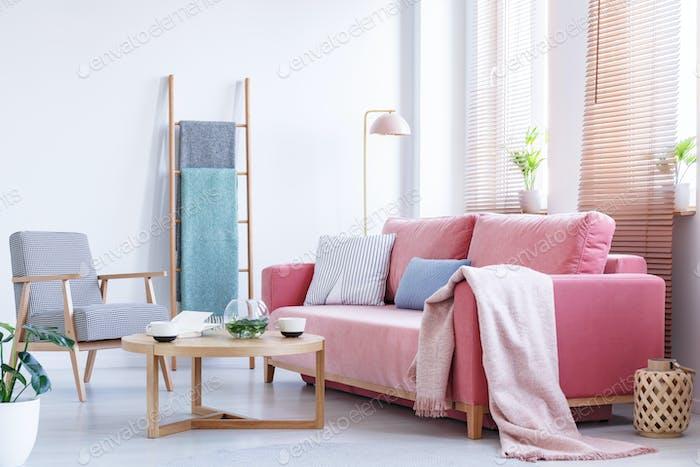 Echtes Foto eine rosa Couch mit Kissen und Decke stehend in einem