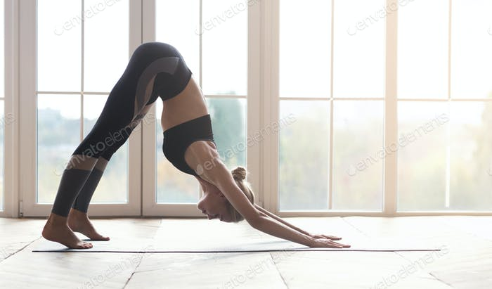 Yoga girl making face down dog pose, side view