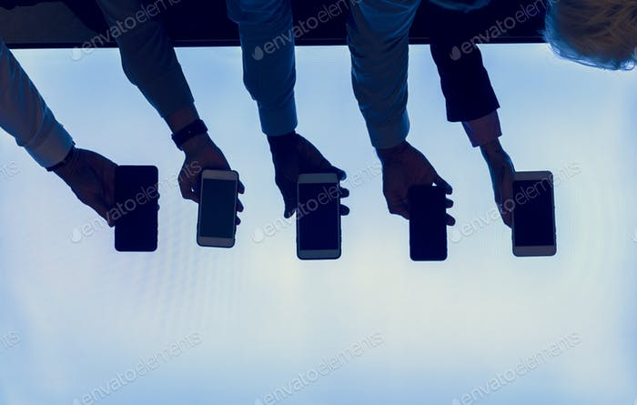 Group of silhouette hands holding smartphone