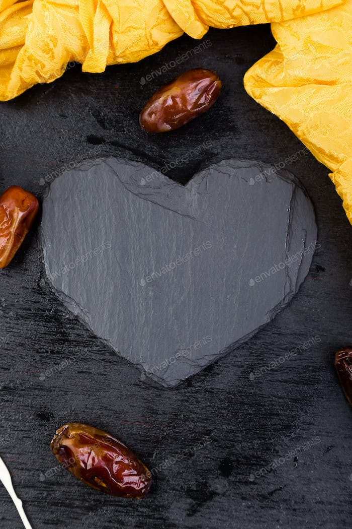 Dry fruit dates in golden cup near slate black heart. Copy space.Valentine Day.
