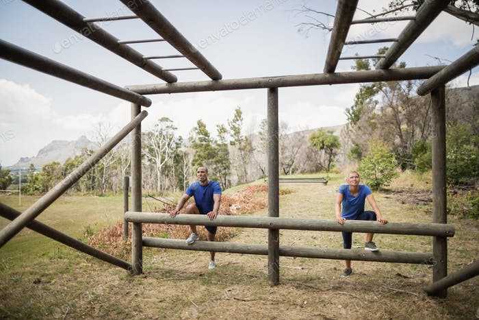 Fit man and woman climbing monkey bars during obstacle course