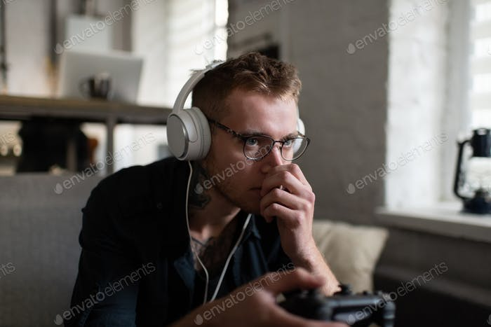 Thoughtful gamer with controller sitting on sofa