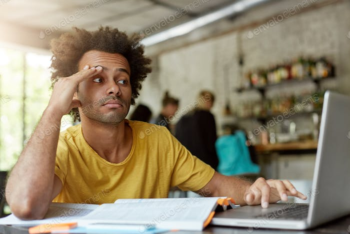 Unhappy black student in casual clothing using wi-fi on laptop computer, looking for information on