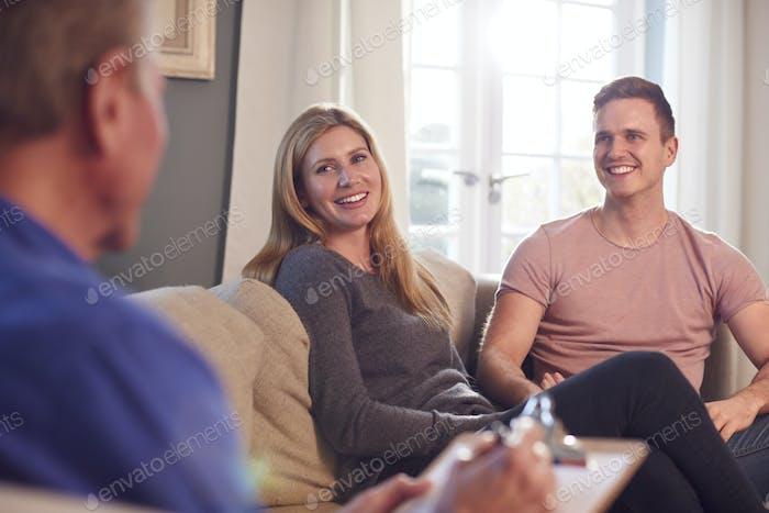 Männlicher Sozialarbeiter mit Zwischenablage, der junges Paar zu Hause besucht