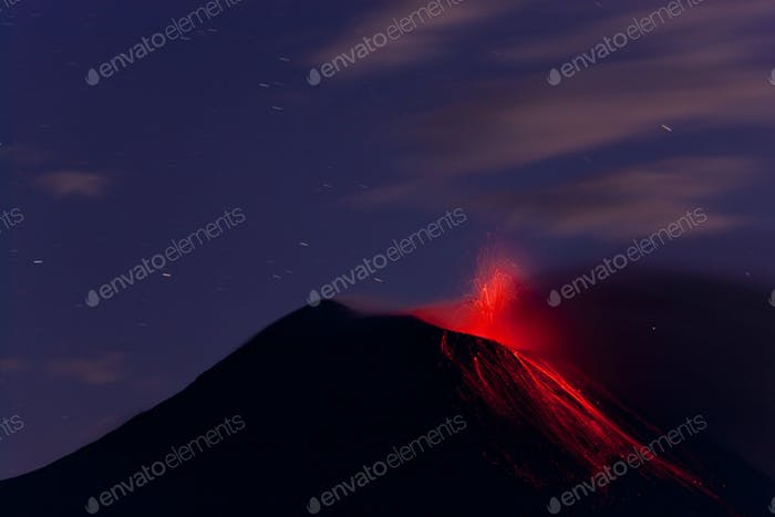 Evening view of fiery eruption of volcano, with lava running down the mountain slopes.