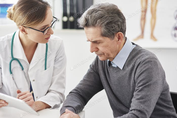 Doctor with digital tablet discusses the results of the senior