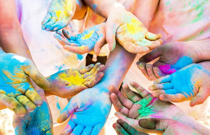 Colorful hands of friends group having fun at beach party on holi color festival
