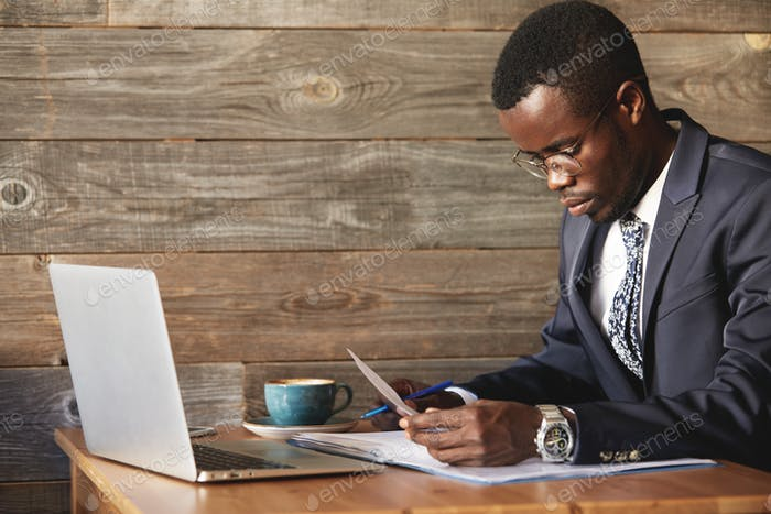 Young and successful businessman looking at contract and reading information in documents with blue