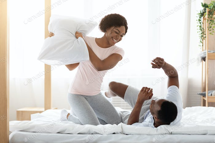 Cheerful loving black couple fighting with pillows in bed
