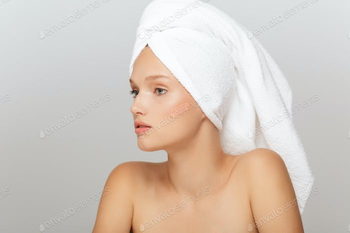 Portrait of young beautiful woman with white towel on head witho