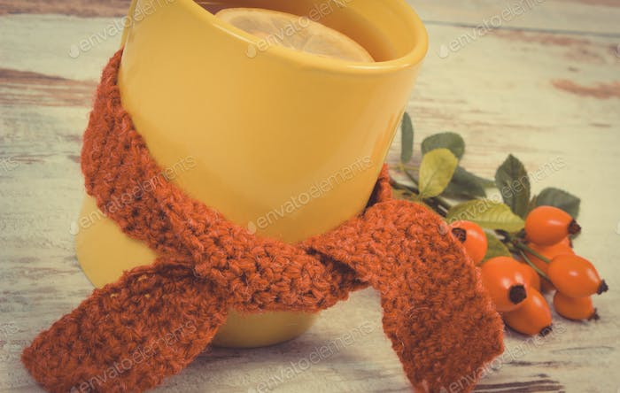 Vintage photo, Cup of hot tea with lemon wrapped woolen scarf, old rustic background