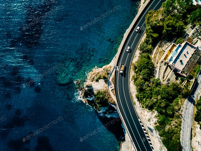 Aerial view of road going along the mountain and ocean or sea.