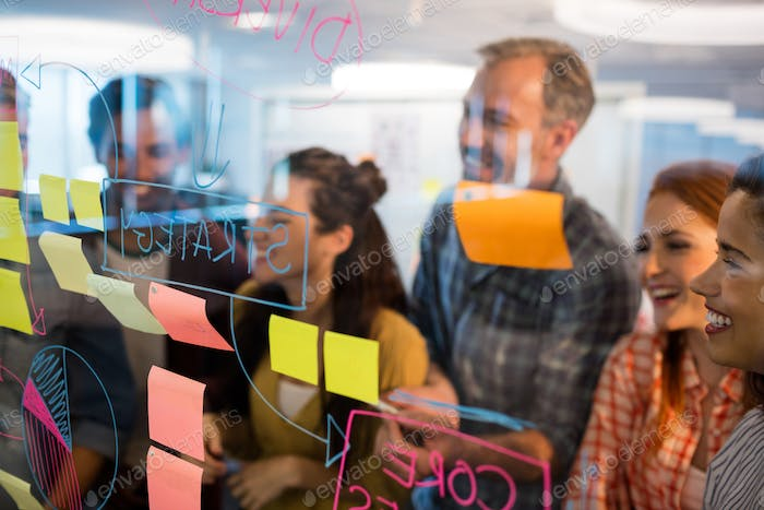 Creative business team looking at sticky notes on glass window