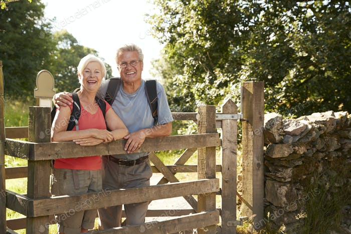 Portrait Of Senior Couple Hiking In Lake District UK Looking Over Wooden Gate
