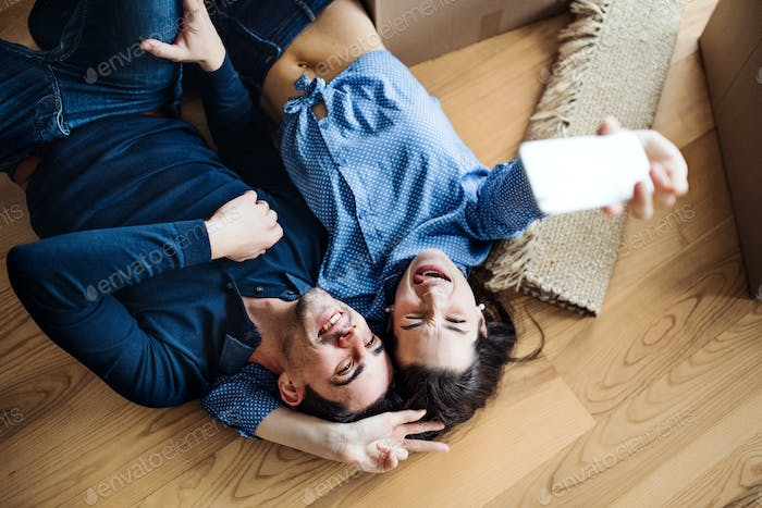 A top view of young couple with a smartphone moving in a new home, taking selfie.